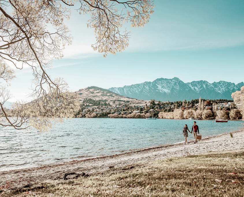 Two people walking on Queenstown Wanaka lakeshore with mountains in background.